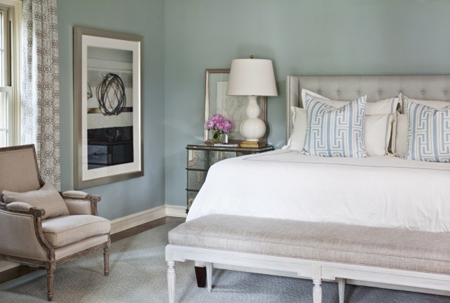 Turquoise bedroom with upholstered headboard, ottoman at the foot of the bed, Louis XIV armchair and a mirrored nightstand