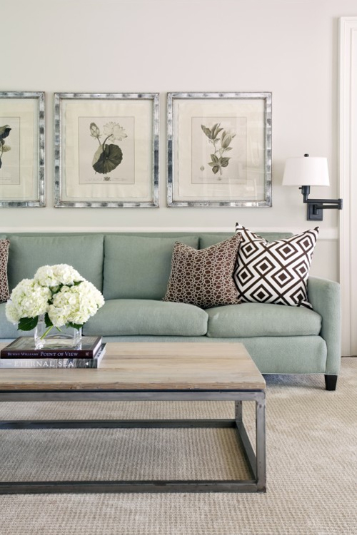 Living room with a sea foam sofa, wall mounted lamps, and a wood coffee table with steel legs