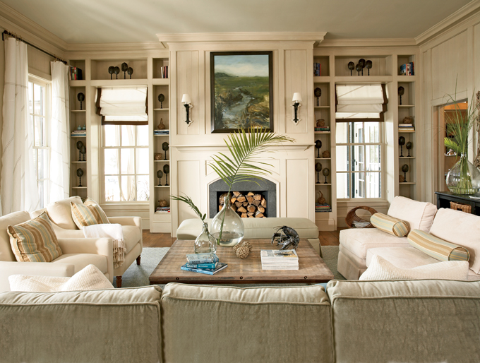 all neutral living room built in shelves around windows flanking fireplace